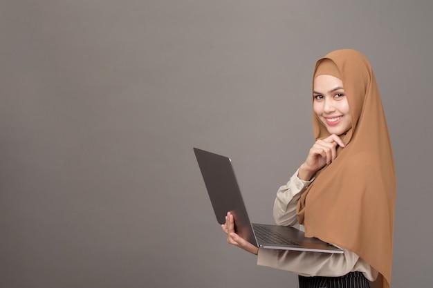 Porträt der schönen frau mit hijab hält computer laptop