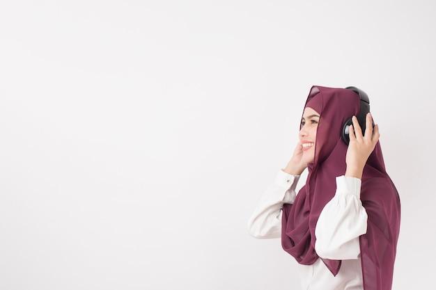 Porträt der schönen frau mit hijab ist genießen musik auf weißem hintergrund zu hören