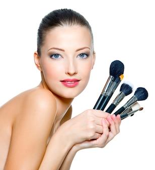 Porträt der schönen frau mit make-up-pinseln nahe attraktivem gesicht. erwachsenes mädchen, das über leerraum aufwirft