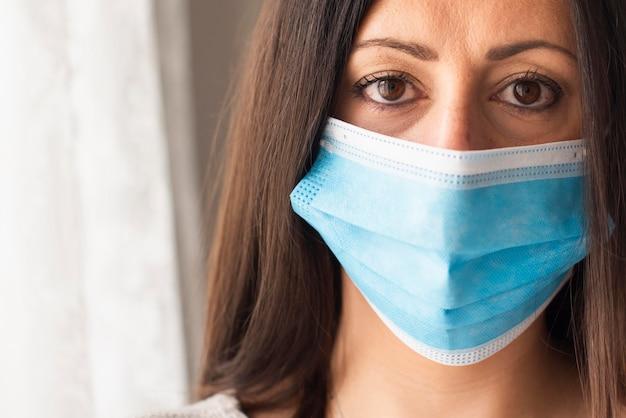 Porträt der schönen frau mit medizinischer maske