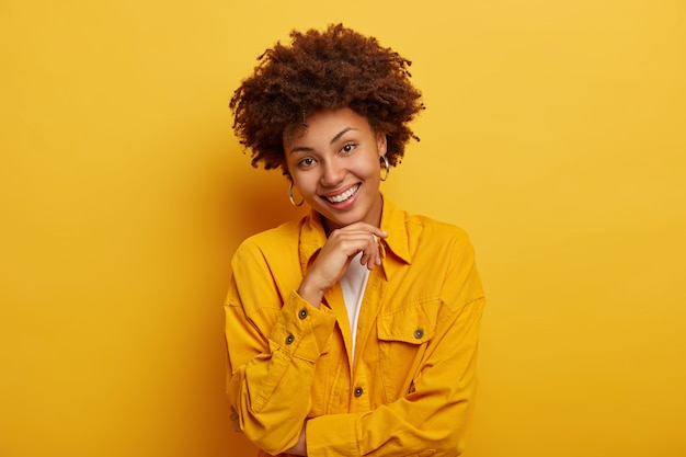 Porträt der schönen frau mit natürlicher schönheit, afro-frisur, trägt leuchtend gelbe jacke, große ohrringe, berührt das kinn, hat sorglosen ausdruck, posiert drinnen im studio.