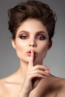 Porträt der schönen frau mit romantischem rotem und goldenem rauchigem augenmake-up, das shh zeichen zeigt
