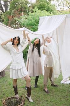 Porträt der schönen frauen am garten, stehend und hält weißes tuch im weißen kleid während des tages.