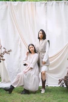 Porträt der schönen frauen im garten, stehend, sitzend und schauend während des tages.