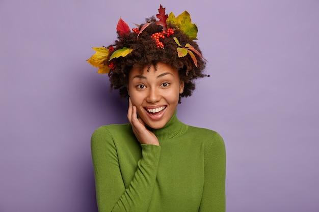 Porträt der schönen fröhlichen afro-frau hält hand auf wange, trägt grünen rollkragenpullover, hat laub in dunklem lockigem haar, lächelt breit, zeigt weiße zähne, hat zartes aussehen