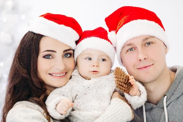 Porträt der schönen fröhlichen familie in den roten hüten und in den pullovern, die vorne lachen und lächeln und sich gegen geschmückten weihnachtsbaum umarmen