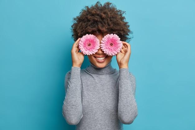 Porträt der schönen fröhlichen frau mit glücklichem ausdruck, hat natürliche schönheit, bedeckt augen mit rosa gerbera-gänseblümchen, gekleidet in lässigen grauen rollkragenposen