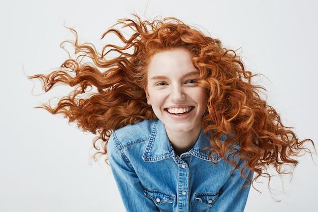 Porträt der schönen fröhlichen rothaarigen frau mit dem fliegenden lockigen haar lächelnd lachend.