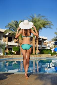 Porträt der schönen gebräunten sportlichen dünnen frau, die im schwimmenhotel-poolbadekurort sich entspannt.