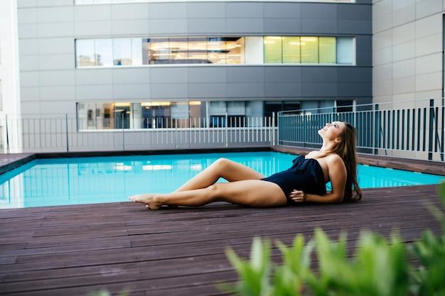 Porträt der schönen gebräunten sportlichen schlanken frau, die im schwimmbad-spa entspannt. kreativer weißer hut und bikini. heißer sommertag und helles sonniges licht.