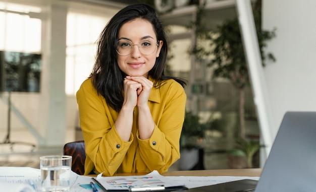 Porträt der schönen geschäftsfrau an ihrem schreibtisch