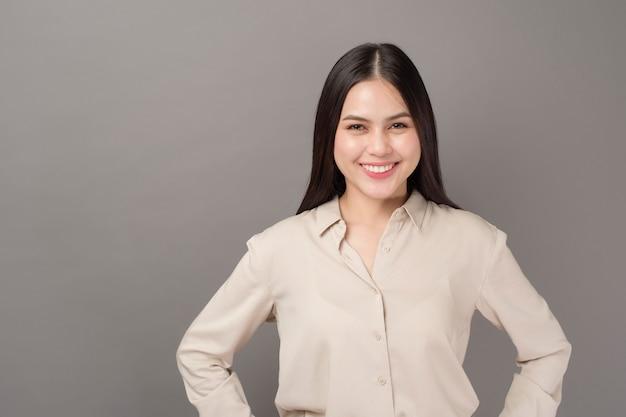 Porträt der schönen geschäftsfrau, die auf grau lächelt