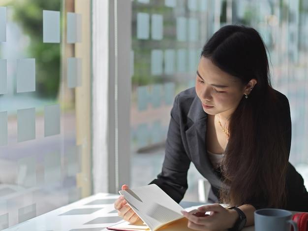 Porträt der schönen geschäftsfrau, die auf notizbuch liest, während sie im büroraum sitzt