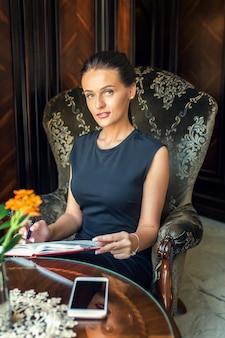 Porträt der schönen geschäftsfrau, die in einem sessel sitzt und notizen auf einem planer zu hause schreibt.