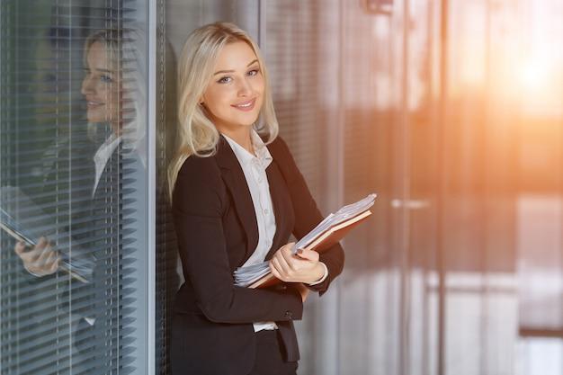 Porträt der schönen geschäftsfrau lächelnd und stehend mit ordner im büro
