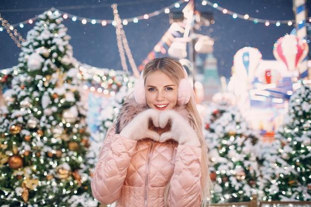 Porträt der schönen glücklichen frau, die herzförmige hände nahaufnahme weiß fäustlinge rosa winter ohrenschützer verschneiter neujahrsbaum und weihnachtsmarkt hält