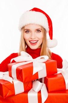 Porträt der schönen glücklichen frau im weihnachtsmannhut, der weihnachtsgeschenke hält