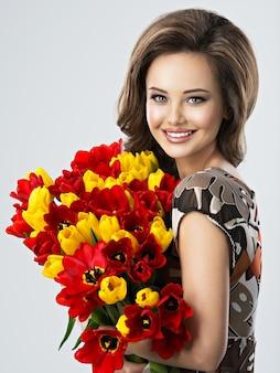 Porträt der schönen glücklichen frau mit blumen in den händen. junges attraktives junges mädchen hält den strauß der roten und gelben tulpen