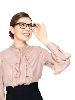Porträt der schönen glücklichen jungen frau in den gläsern, die oben auf weißem hintergrund suchen