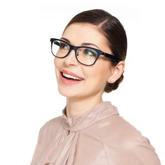 Porträt der schönen glücklichen jungen frau in den gläsern und im beigen hemd, die oben auf weißem hintergrund suchen