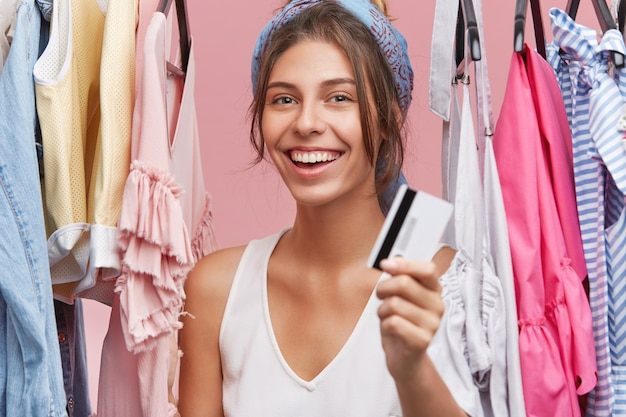 Porträt der schönen glücklichen jungen kaukasischen frau, die plastikkreditkarte zeigt und fröhlich lächelt, sich über einkaufen und neue einkäufe aufgeregt fühlt, im laden unter kleidern stehend