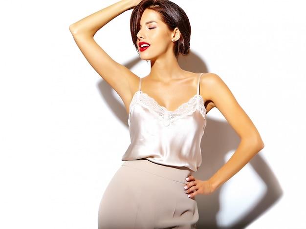Porträt der schönen glücklichen netten sexy brunettefrau mit den roten lippen in den breiten klassischen hosen auf weißem hintergrund