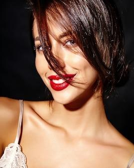 Porträt der schönen glücklichen netten sexy brunettefrau mit den roten lippen in der pyjamawäsche auf schwarzem hintergrund