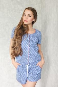Porträt der schönen glücklichen netten sexy brunettefrau mit den roten lippen in der pyjamawäsche