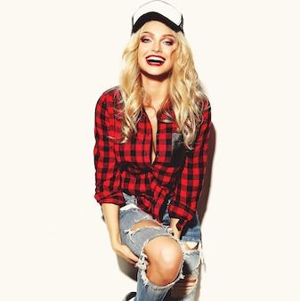 Porträt der schönen glücklichen niedlichen lächelnden blonden frau böses mädchen im lässigen roten hipster winter karierten flanellhemd und blue jeans kleidung mit roten lippen und mütze