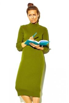 Porträt der schönen glücklichen niedlichen lächelnden brünetten studentin in lässiger grüner hipster-sommerkleidung lokalisiert auf weißem halten des blauen stiftes mit buntem notizbuch, denkend während des studiums