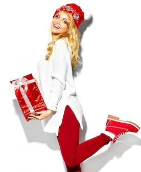 Porträt der schönen glücklichen süßen lächelnden blonden frau frau, die in ihren händen große weihnachtsgeschenkbox in lässiger roter hipster-winterkleidung hält, im weißen warmen pullover, der auf einem bein steht