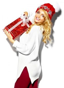 Porträt der schönen glücklichen süßen lächelnden blonden frau frau, die in ihren händen große weihnachtsgeschenkbox in lässiger roter hipster-winterkleidung, im weißen warmen pullover hält