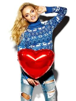 Porträt der schönen glücklichen süßen lächelnden blonden frau frau, die in ihren händen großen roten herzballon in der lässigen warmen winterkleidung des lässigen hipsters im blauen pullover hält