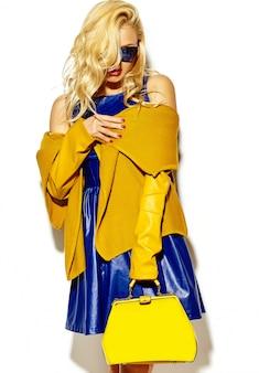 Porträt der schönen glücklichen süßen lächelnden blonden frau frau in lässigen hipster warmen pullover kleidung, mit gelber handtasche in sonnenbrille