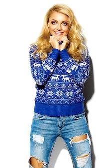 Porträt der schönen glücklichen süßen lächelnden blonden frau in der warmen winterkleidung des lässigen hipsters, im blauen pullover mit hirschen