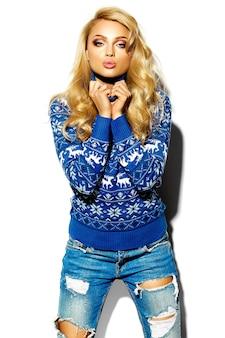 Porträt der schönen glücklichen süßen lächelnden blonden frau in der warmen winterkleidung des lässigen hipsters im blauen pullover