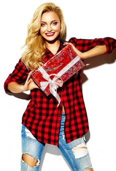 Porträt der schönen glücklichen süßen lächelnden blonden frau mädchen, die in ihren händen weihnachtsgeschenkbox in lässigen roten hipster winter karierten flanellhemd kleidung und blue jeans hält