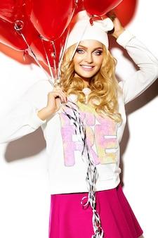 Porträt der schönen glücklichen süßen niedlichen lächelnden blonden frau in lässigen hipster-kleidern, im rosa rock und in der warmen wintermütze mit roten herzballons in den händen