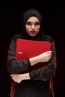 Porträt der schönen hoffnungslosen erschrockenen erschrockenen jungen moslemischen frau, die das schwarze hijab hält ordner als das halten des geheimen konzeptes trägt