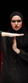 Porträt der schönen hoffnungslosen erschrockenen erschrockenen jungen moslemischen frau, die das schwarze hijab zeigt stoppschild auf schwarzem trägt