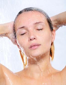Porträt der schönen hübschen jungen frau, die dusche nimmt