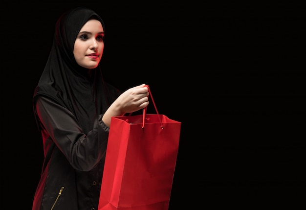 Porträt der schönen intelligenten jungen moslemischen frau, die angeboteinkaufstasche des schwarzen hijab als verkäufer auf schwarzem trägt