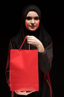Porträt der schönen intelligenten jungen moslemischen frau, die angebotseinkaufstasche des schwarzen hijab als verkäufer trägt