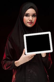 Porträt der schönen intelligenten jungen moslemischen frau, die das schwarze hijab hält tablette in ihren händen als bildungskonzept trägt