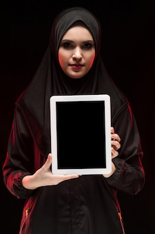 Porträt der schönen intelligenten jungen moslemischen frau, die das schwarze hijab hält tablette in ihren händen trägt