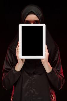 Porträt der schönen intelligenten jungen moslemischen frau, die das schwarze hijab hält tablette trägt