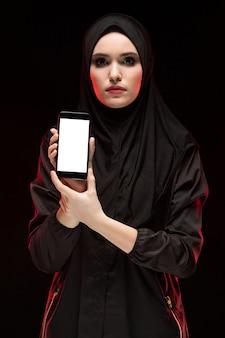 Porträt der schönen intelligenten jungen moslemischen frau, die schwarzen hijab werbungshandy in ihren händen als bildungskonzept trägt