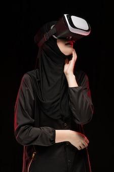 Porträt der schönen intelligenten jungen moslemischen frau, die schwarzes hijab unter verwendung des kopfhörers der virtuellen realität auf schwarzem hintergrund trägt
