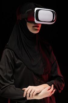 Porträt der schönen intelligenten jungen moslemischen frau, die schwarzes hijab unter verwendung des kopfhörers der virtuellen realität auf schwarzem trägt