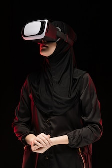 Porträt der schönen intelligenten jungen moslemischen frau, die schwarzes hijab unter verwendung des kopfhörers der virtuellen realität trägt